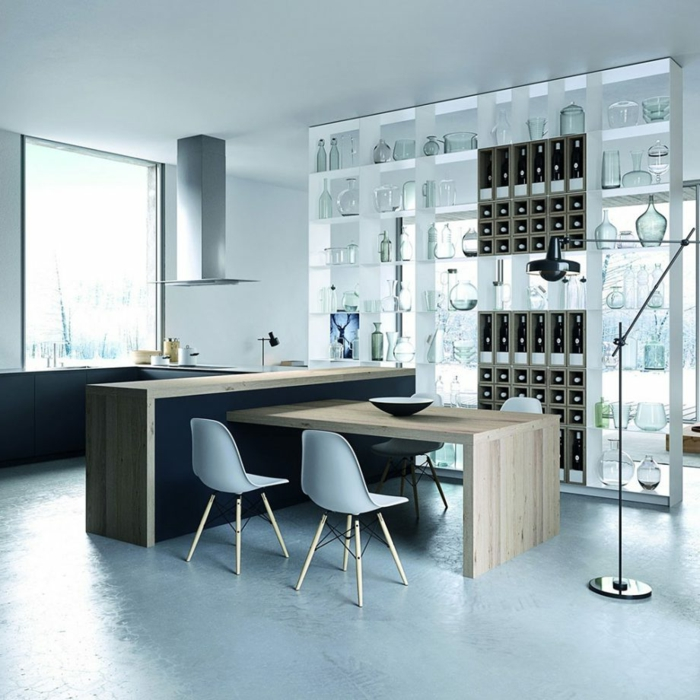 ein Raumteiler mit Regalen, eine Kochinsel aus Holz, ein Tisch mit vier weißen Stühlen, Boden Betonoptik