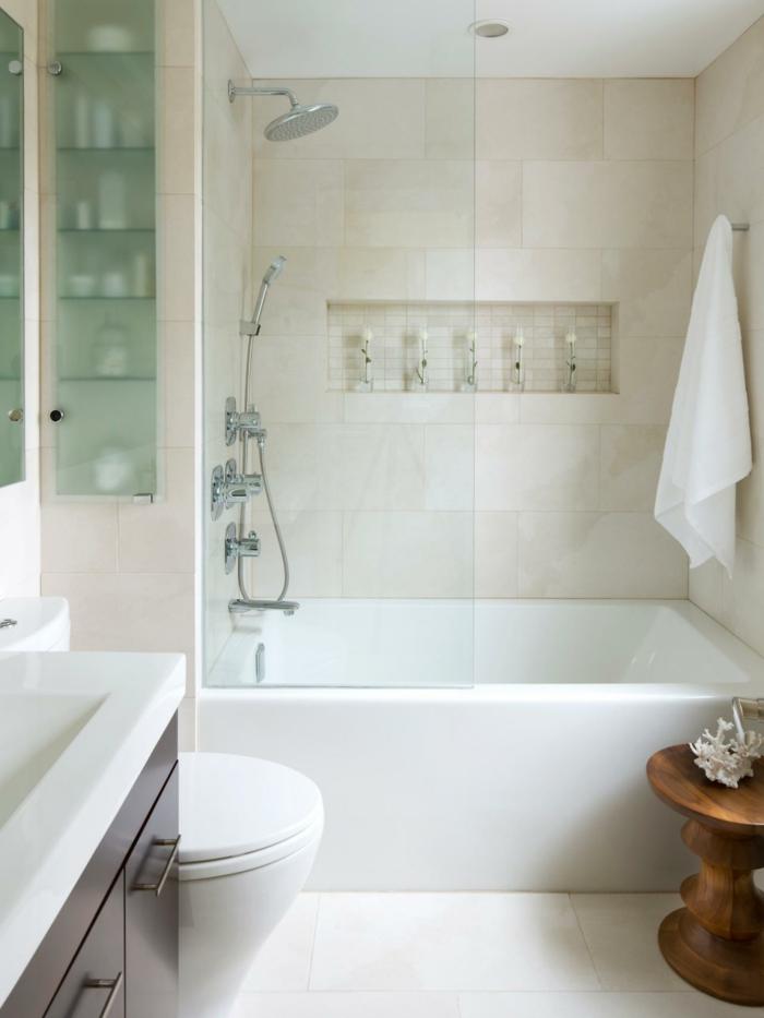 eine kleine Badewanne, große weiße Fliesen als Bodenbelag, beige Fliesen an den Wänden