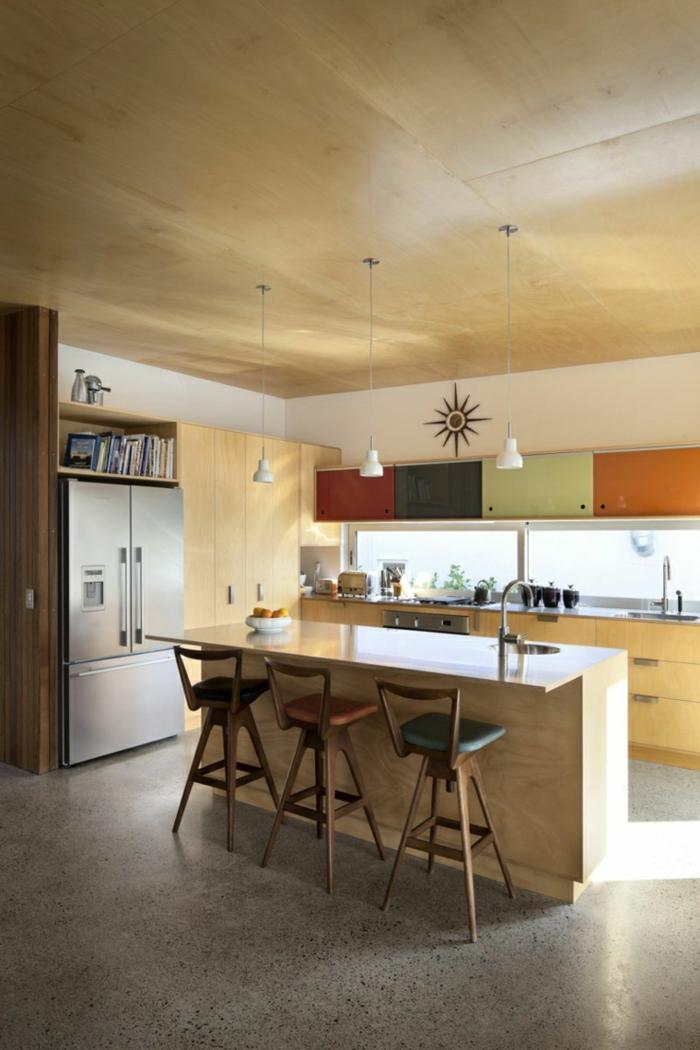 bunte Regale, ein Kochinsel aus Holz, drei Hocker, drei Pendelleuchten, Küchenschränke, Boden Betonoptik