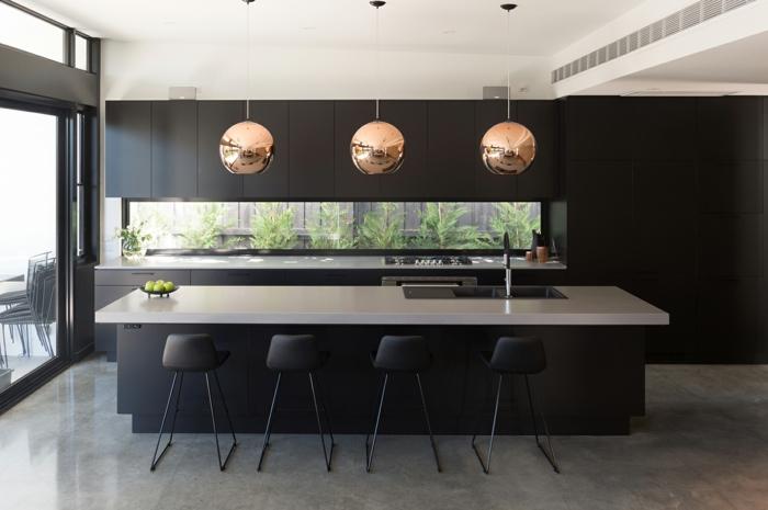 runde Pendelleuchte, eine lange Kochinsel mit vier Hocker, ein Luxus Küche mit Boden Betonoptik