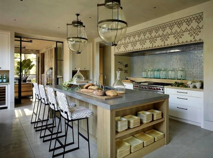 eine moderne Küche, Boden Betonoptik, runde Lampe aus Glas, graue Kochinseln mit schwarz weiße Hocker
