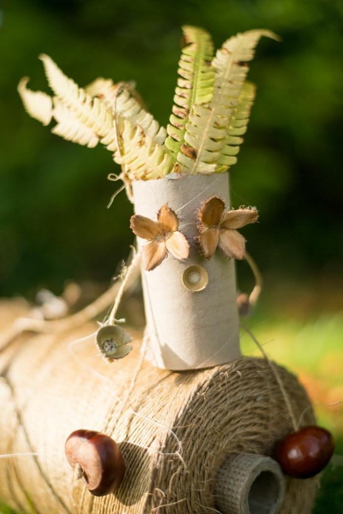 eine Stringpuppe aus Klopapierrollen und Kastanien aus Beinen, Kastanienfiguren mit Gras als Haar