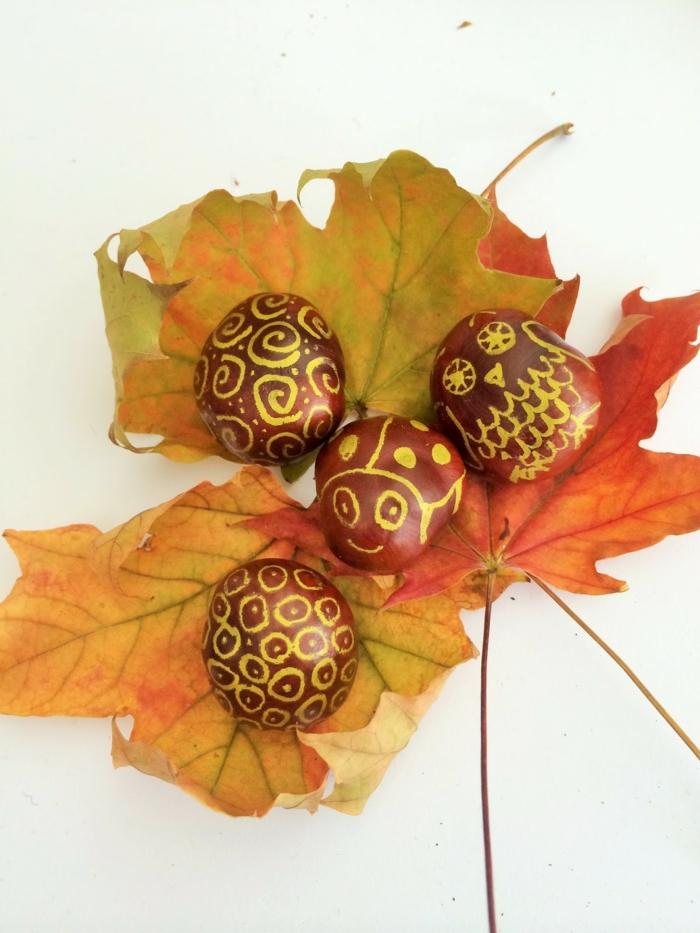 die vier mit goldenen Filzstift bemalten Kastanien, drei gelbe Blätter, Kastanienfiguren
