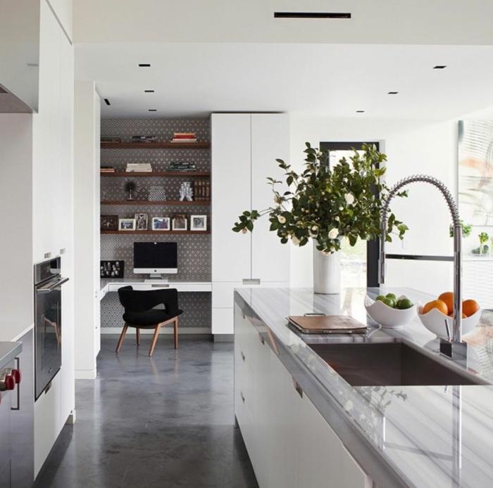 Fußboden Betonoptik, Marmor Kochinsel, braune Regale, eine Vase mit grünen Pflanzen