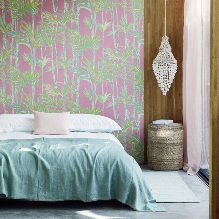 ein modernes Schlafzimmer, eine hängende Lampe, ein blauer Teppich, Fototapete in rosa und grüner Farbe, Fußboden Betonoptik