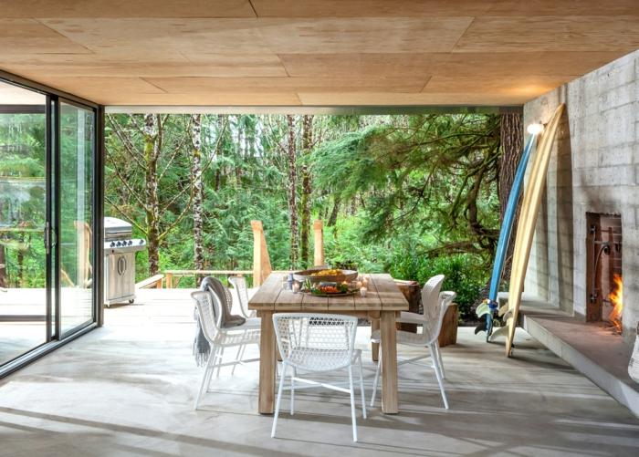 eine schöne Terrasse von Ferienhaus im Wald, ein hölzerner Tisch und ein Kamin, Fußboden Betonoptik
