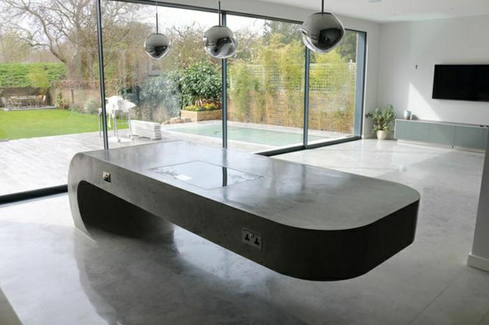 eine schöne Theke, drei Pendelleichten, Fußboden Betonoptik, Fenster zum Garten, Fernseher im Hintergrund