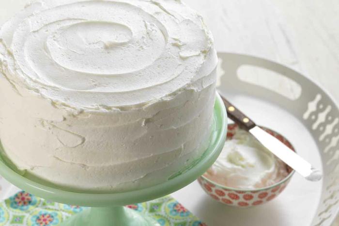 schneller Kuchen mit weißen Vanillie Creme dekoriert mithilfe eines kleinen Messers