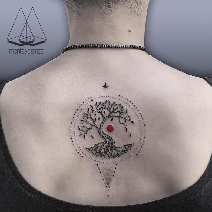 eine graue wand und eine frau mit einer schwarzen kette und einem rücken mit einem schwarzen lebensbaum tattoo mit einer kleinen roten sonne und sternen