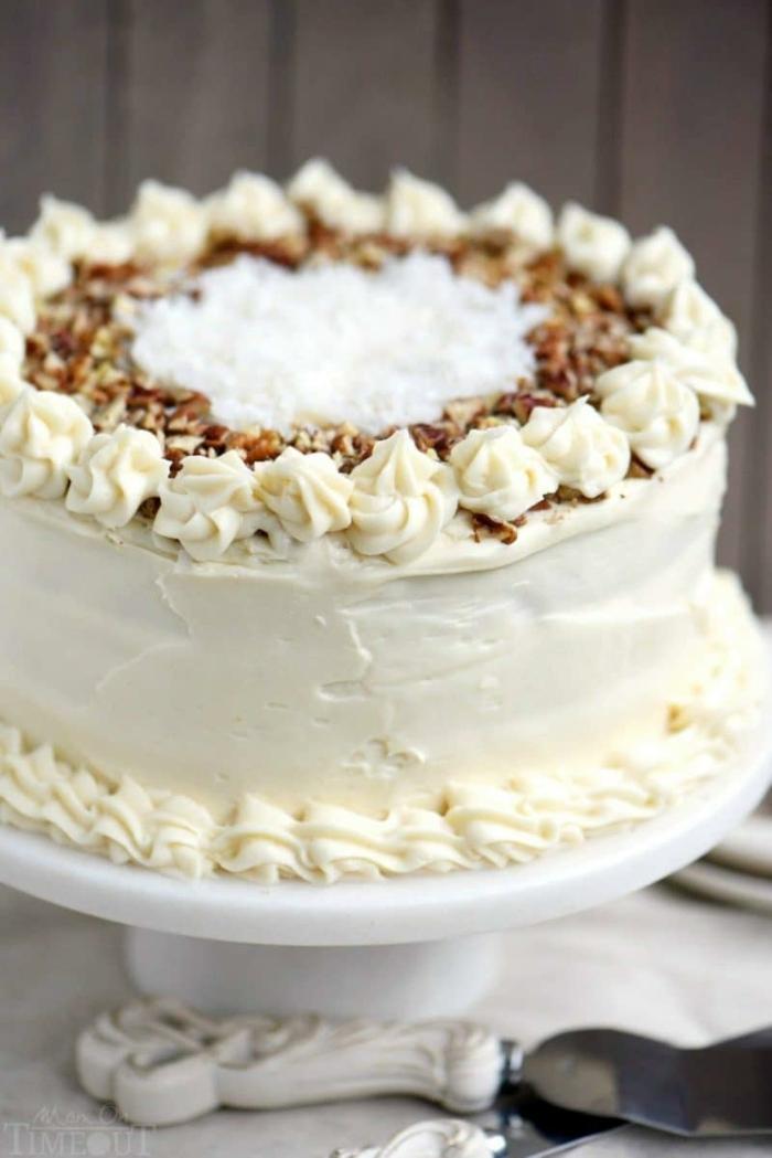 Torte mit weißer Creme, mit zerkrümelte Nüssen bestreut, Kokosraspeln in der Mitte, schneller Kuchen