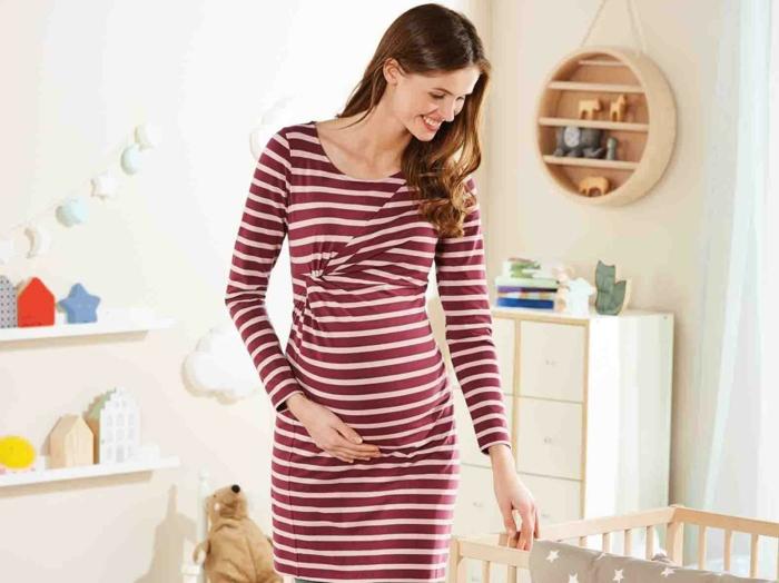 Schwangerschaftskleider festlich, gestreiftes rotes Kleid, eine werdende Mutter im Babyzimmer