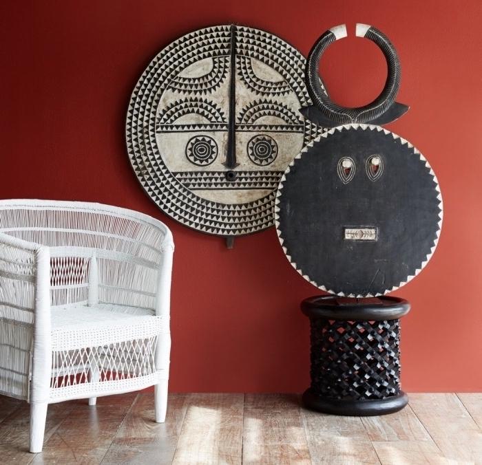 dekorationen und wohnzimmer einrichtung, rote wand und schwarz weiße elemente daran, sessel in weiß, hocker in schwarz