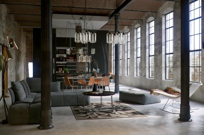 eine enorme Einzimmerwohnung, ein runder Tisch, graues Sofas, ein weißer Schaukelstuhl