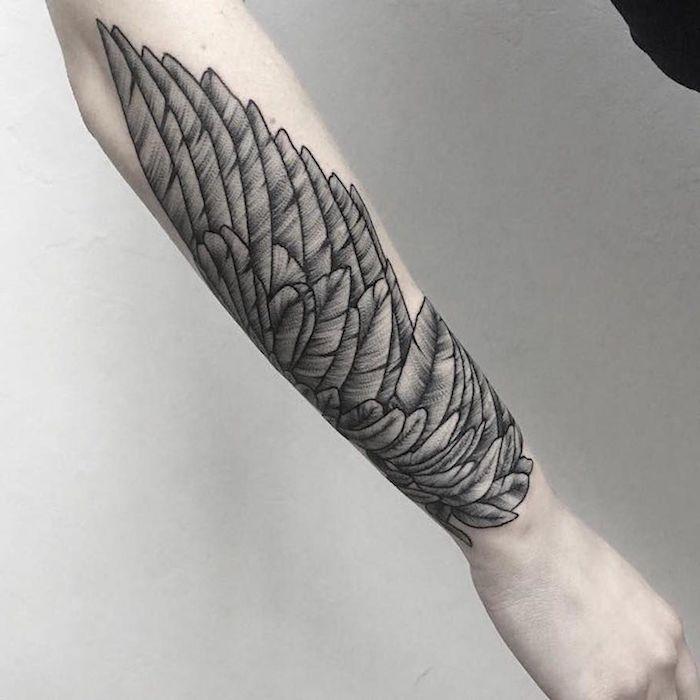 engelsflügel tattoo arm, schwarz graue tätotiwierung am unterarm, feder