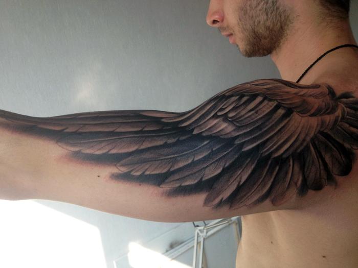 mann mit 3d tätowierung, engelsflügel tattoo arm, schwarz grau, realitisch