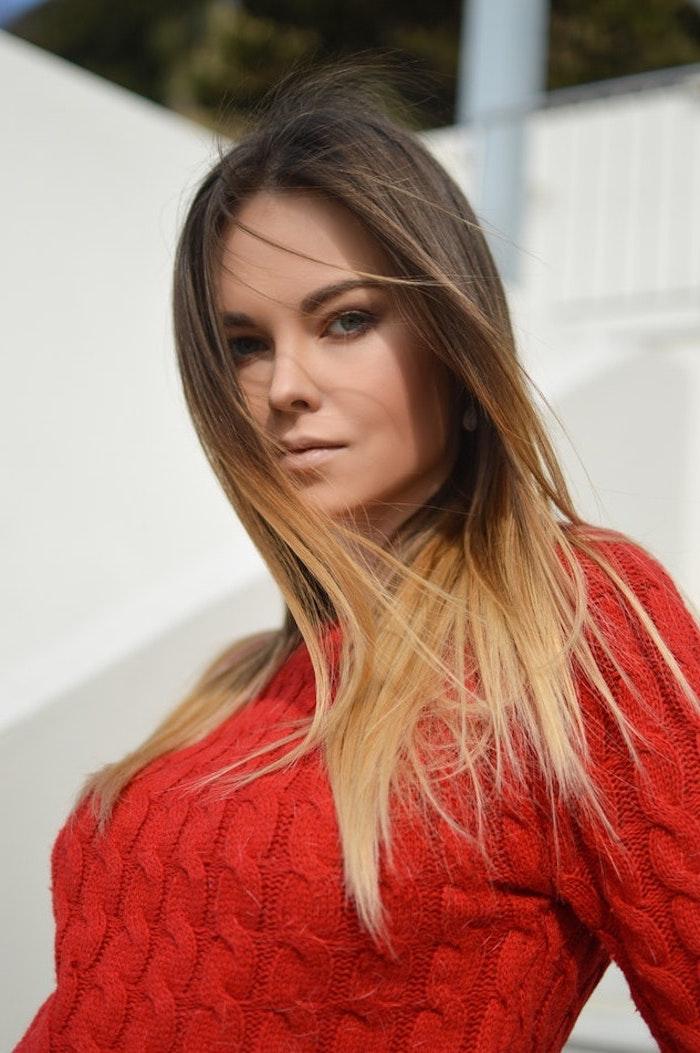 mittellange haare schnitt ideen mit ombre oder balayage, eine frau mit rotem pulli, pullover, gestrickt, tägliches make up