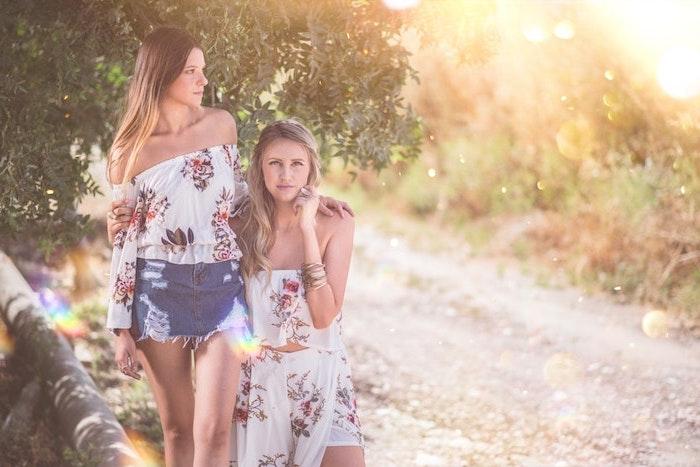 feines haar style von zwei damen in der natur spazieren gehen, im sommer besondere pflege gegen die sonne
