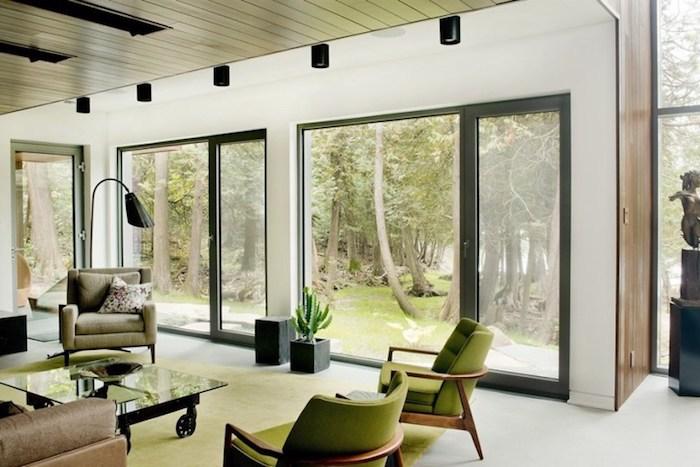 wandgestaltung wohnzimmer, naturnahes interieur, grüne sessel, fenster, wand aus glas