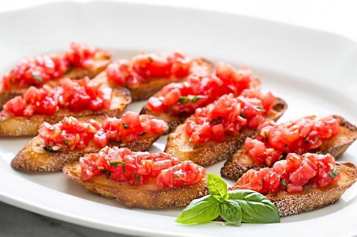 fingerfood ideen, bruschettas mit basilikum und tomaten, großer weißer teller, vorspeise