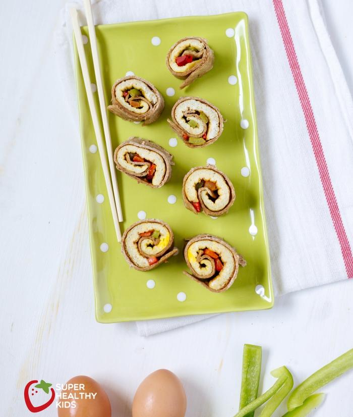fingerfood kalt, sushi rollen, eckiger grüner teller mit weißen punkten, hozstäbchen