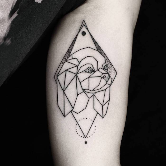 hand mit einem großen geometrischen arm tattoo mit einem weißen hund mit einer weißen nase und einem schwarzen mond