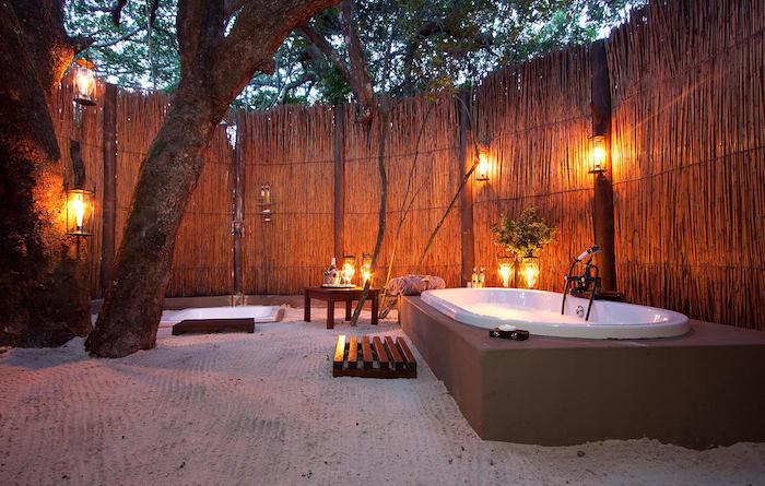weiße kleinen badewanne im garten mit einem baum und sichtschutz aus holz, baum mit grünen blättern und viele kleine orange und gelbe kerzen