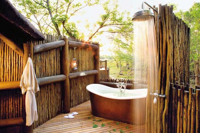 boden aus holz und eine weiße badewanne, sichtschutz gartendusche aus holz, wände aus holz, garten mit grünen bäumen mit gränen blättern