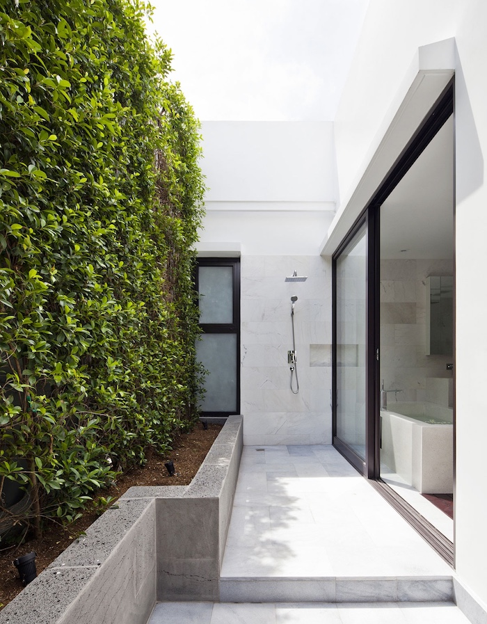 boden aus weißen fliesen, garten mit pflanzen mit grünen blättern, weißes haus mit garten mit einer gartendusche solar