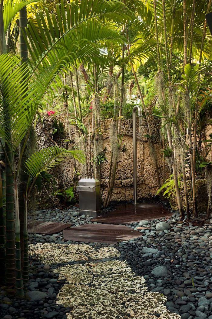 boden aus vielen grauen kleinen steinen, garten mkt palmen mit grünen blättern und mit einer gartendusche
