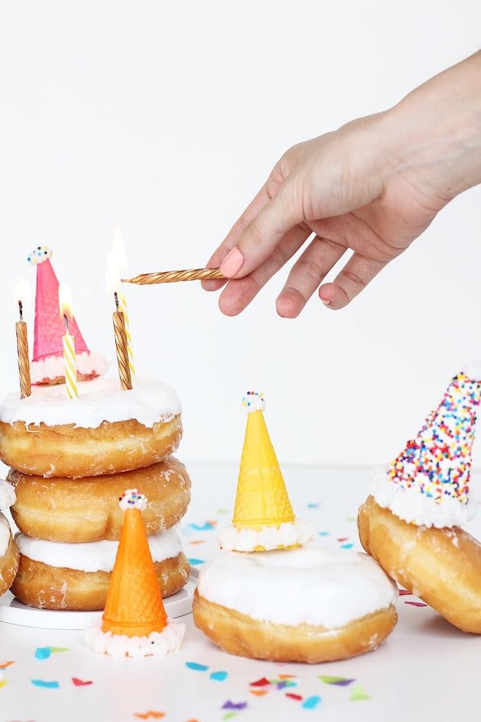 Donuts mit weißer Glasur anstatt Geburtstagstorte, kleine Waffeln mit Zuckerstreuseln, goldene Kerzen