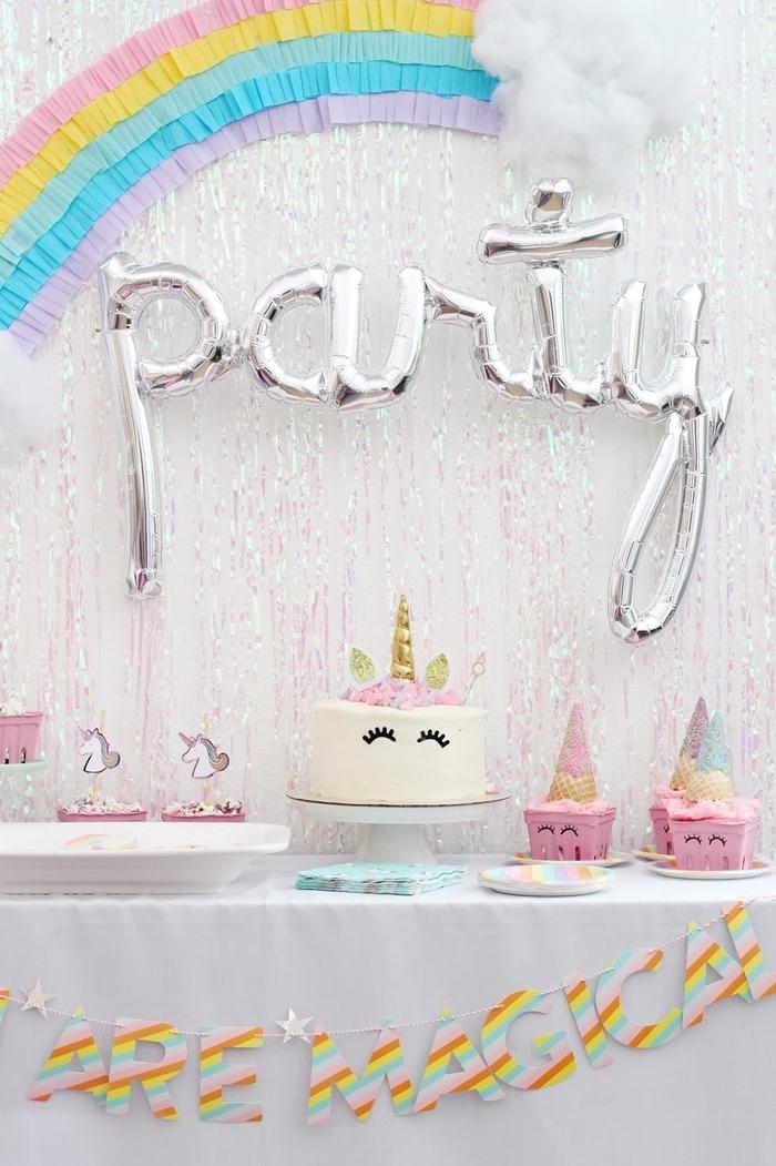 Geburtstagsthema Einhorn, Regenbogen aus Papier an der Wand, Torte als Einhorn