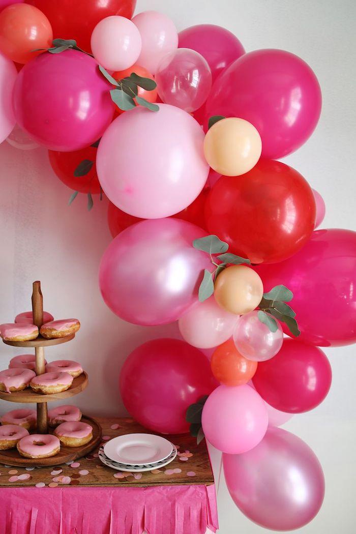 Bogen aus violetten Ballons, Donuts mit Erdbeerglasur, Blütenblätter auf dem Tisch