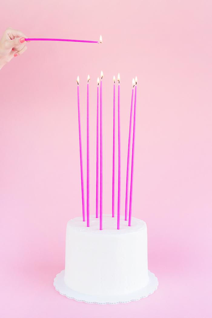 Geburtstagstorte mit weißer Glasur, hohe violette Kerzen, Geburtstag für Mädchen planen