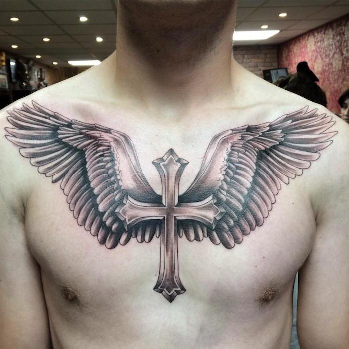 gedenk tattoo an der brust, großer kreuz mit engelsflügeln, religiöses motiv, mann