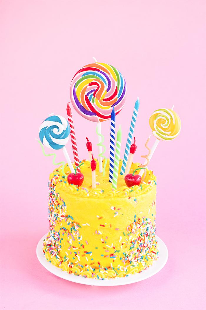 Geburtstagstorte mit gelber Glasur und Zuckerstreuseln, bunte Kerzen und Lutscher