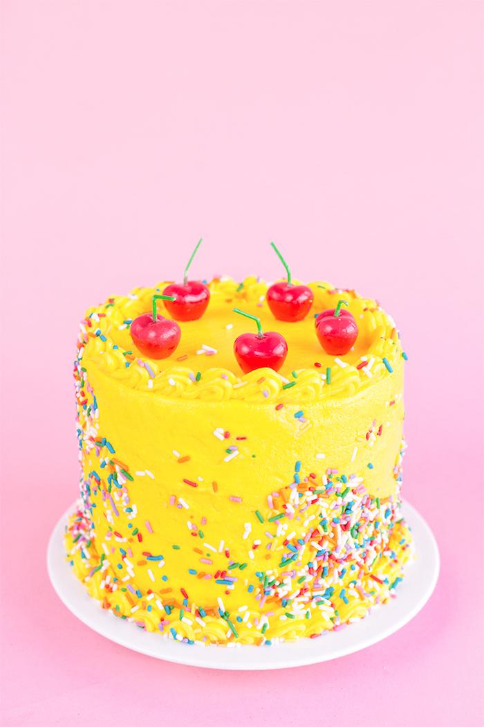 Schöne Geburtstagstorte mit gelber Glasur und Zuckerstreuseln, Kerzen in Form von Kirschen