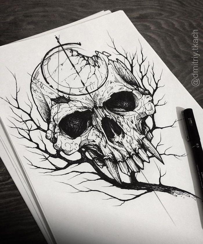 ein tisch aus holz und ein weißes blatt papier mit einem schwarzen baum, ein totenkopf tattoo mit inem schädel mit scharfen zähnen