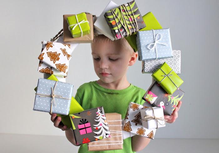 geschenkbox weihnachten, kleiner junge, weihanchtskranz aus geschenkboxen