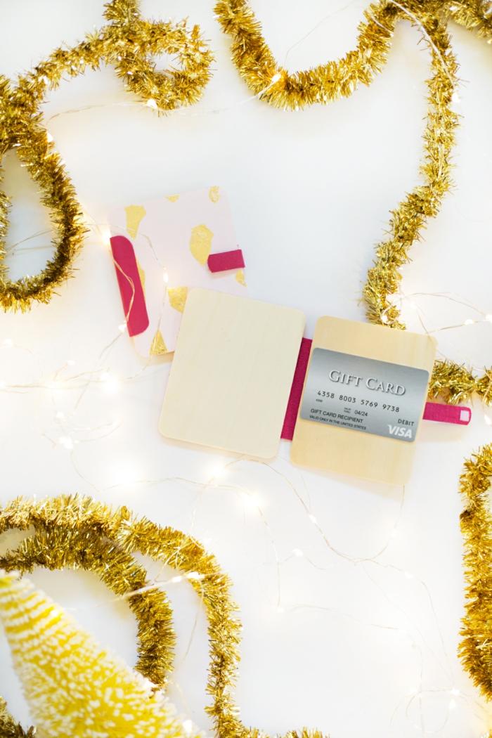 ein grauer Gutschein in einer Verpackung aus Holz, Girlande darum, Geschenke schön verpacken