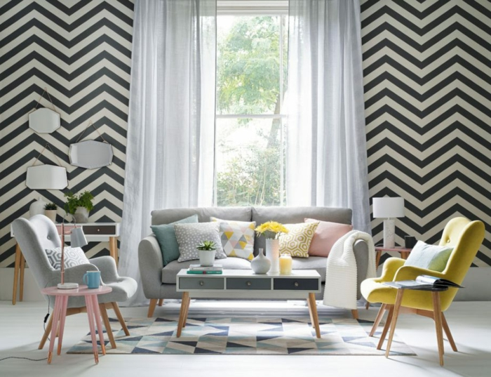 Betonboden Wohnbereich, ein modernes Wohnzimmer, graues Sofa, zwei Sessel, gelb und grau, viele kleine Spiegel