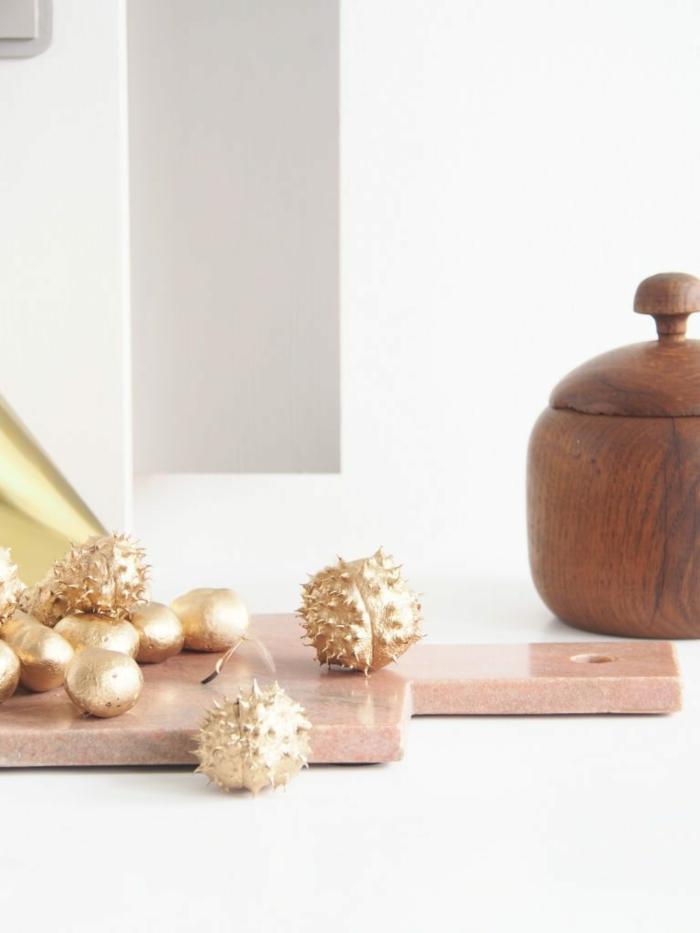 ein Komposition aus goldenen Kastanien, ein Brett und ein Gefaß aus Holz, Basteln mit Kastanien