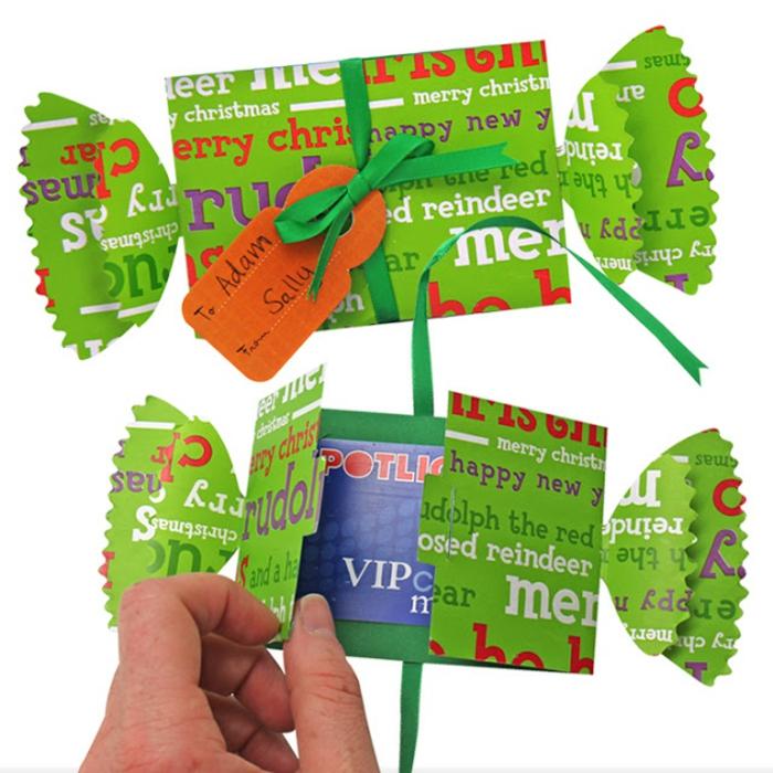 grüne Bonbonverpackungen, darin steckt eine blaue Karte, orange Anhänger, Geschenke originell verpacken