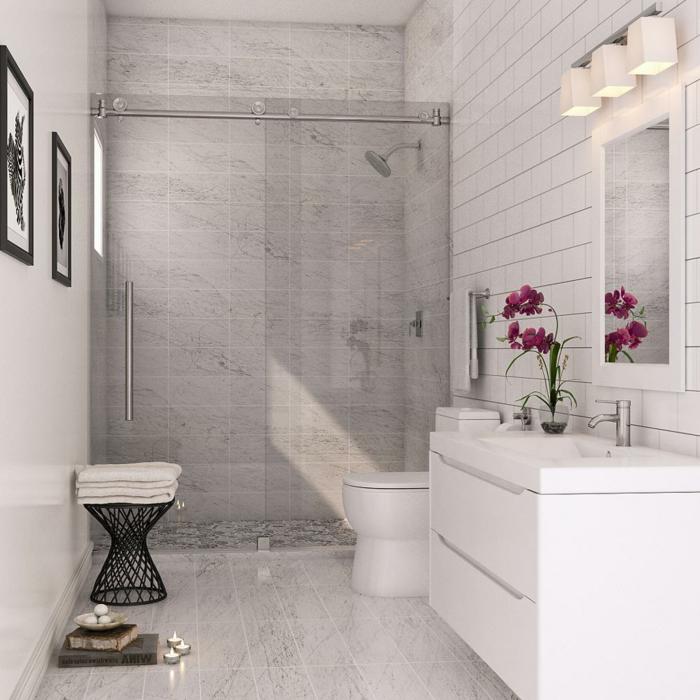 eine graue Duschkabine, weiße Bodenfliesen, Minibad, eine rosa Blume, schwarz weiße Bilder