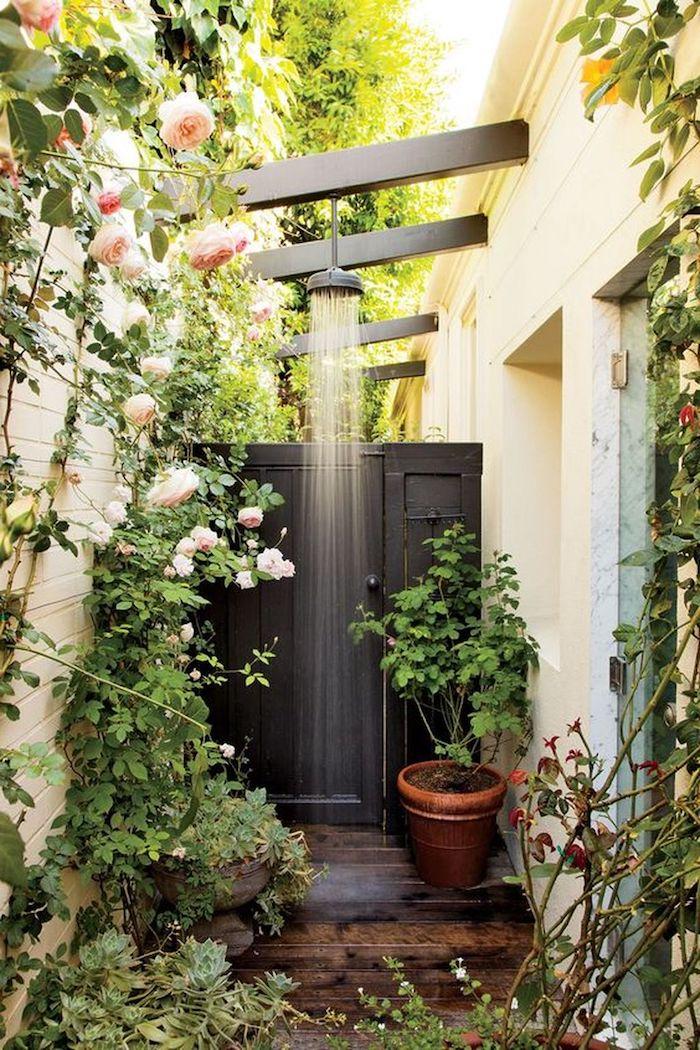 braune blumentöpfe mit grünen pflanzen und blättern, ein gelbes haus und eine graue dusche, garten mit pinken und weißen rosen mit grünen blättern