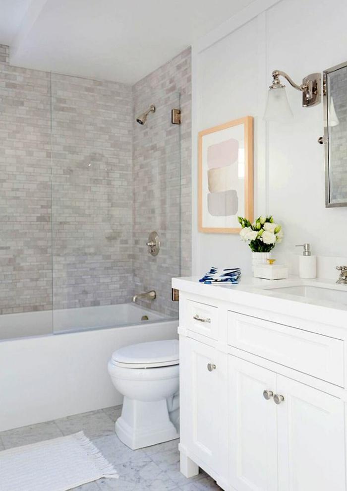 Minibad mit einer Badewanne, ein Bild mit orangen Rahmen, graue Fliesen am Boden
