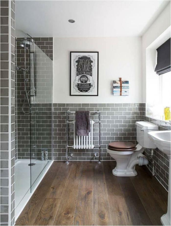 Laminat Bodenbelag, graue Fliesen wie Backsteinen an den Wände, eine Duschkabine, Minibad