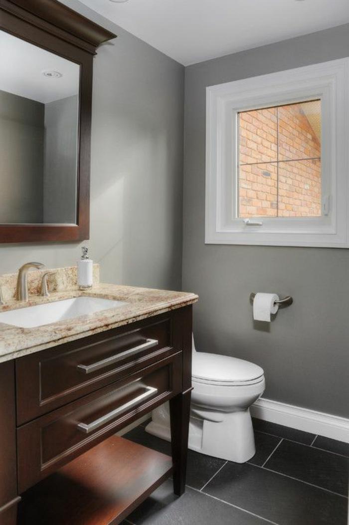eine graue Wand, schwarzer Boden, ein Waschbecken mit braunen Unterschränken, günstige Badmöbel für kleine Bäder