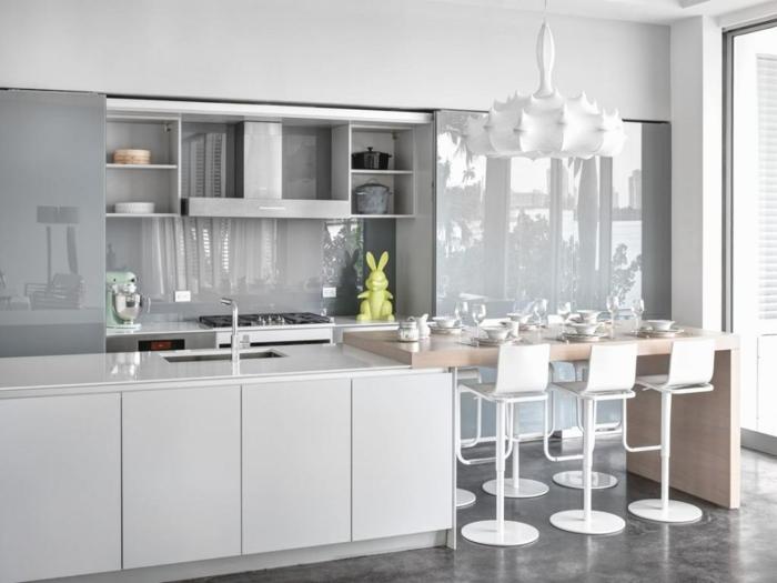 eine Kochinsel, Theke mit sechs Stühle, ein graues Regal, eine weiße Lampe, Betonboden Wohnbereich