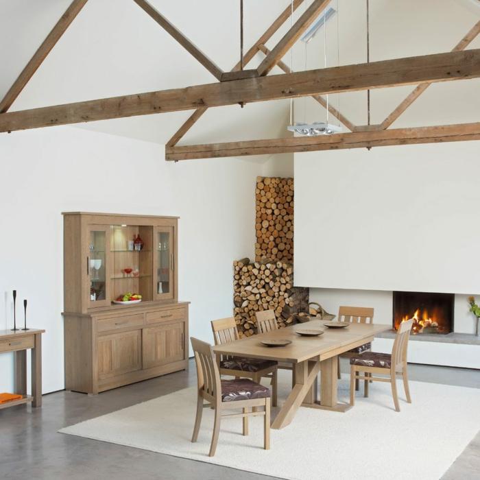 ein Kamin mit Feuer, ein Regal, Tisch und Stühle aus Holz, Balkendach, Betonboden Wohnbereich