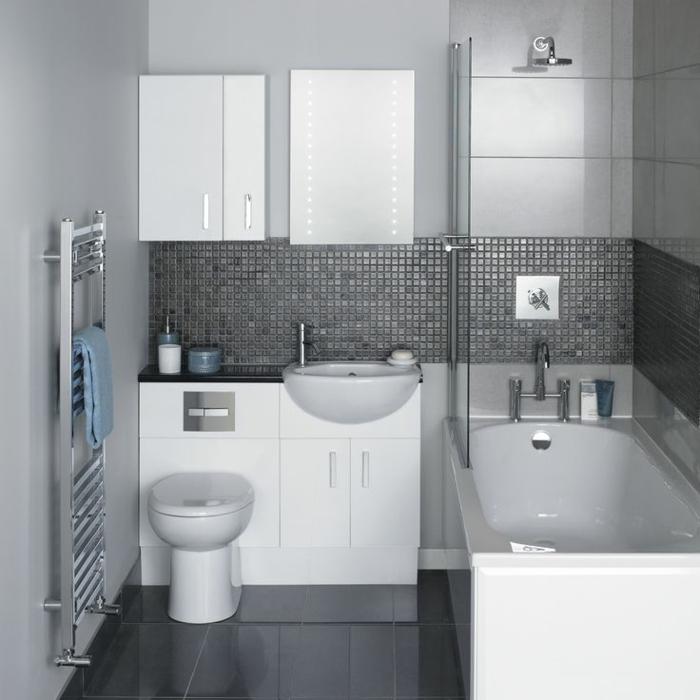grauer Fliesenboden, graue Mosaikfliesen an den Wänden, Minibad, eine schöne weiße Badewanne, Spiegelschrank mit LED Beleuchtung